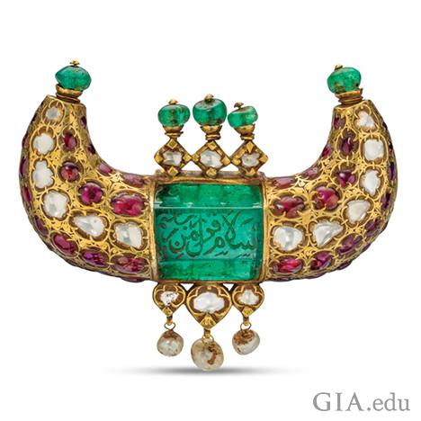 エメラルド、ルビー、ダイヤモンド、真珠を特徴とし、アラビア語での彫刻が見られる角の形をした宝石ペンダント。