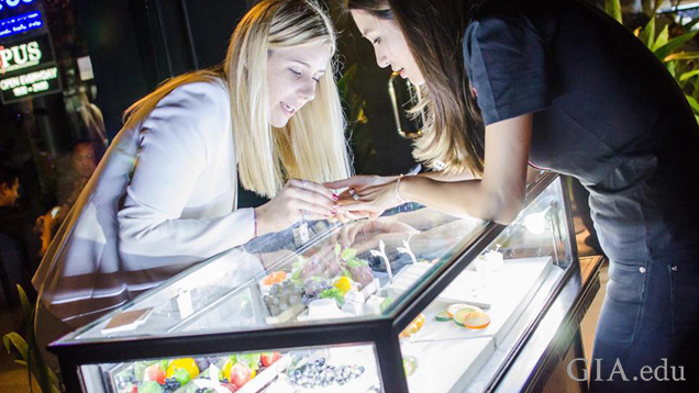 Two women look at jewelry on top of a jewelry display case.