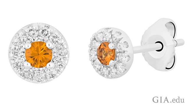 A close up of a pair of stud earrings. Center stone is an orange sapphire, surrounded by colorless diamonds.