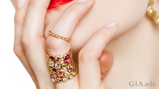 A woman's hand rests on her chin and mouth – she has several multi-color gem rings stacked on her ring finger.