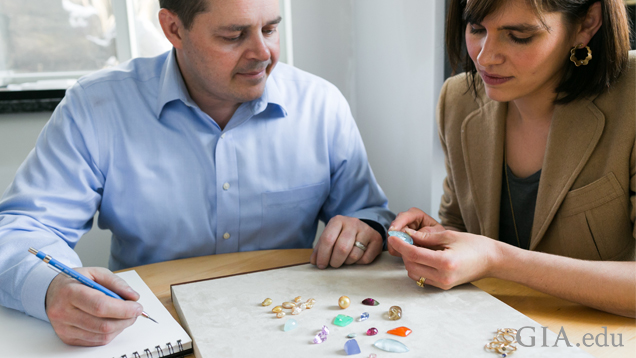 A man and a woman sit at a table with a couple of dozen gems in front of them. They are looking at them and making notes.