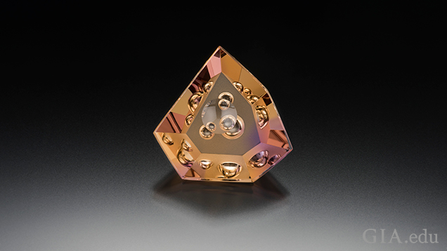 "A triangular shaped piece of ametrine (yellow and purple) with ""bubbles"" of internal carvings."