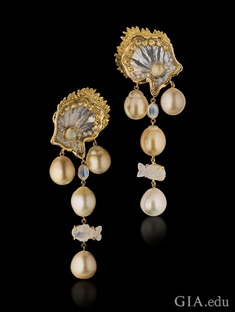 South Sea pearls dangle from clam-shapes made from mother of pearl and accented with white and yellow sapphires and 18K yellow gold. Moonstone accents, including one fish-shaped item, also dangle from the top of the earrings.