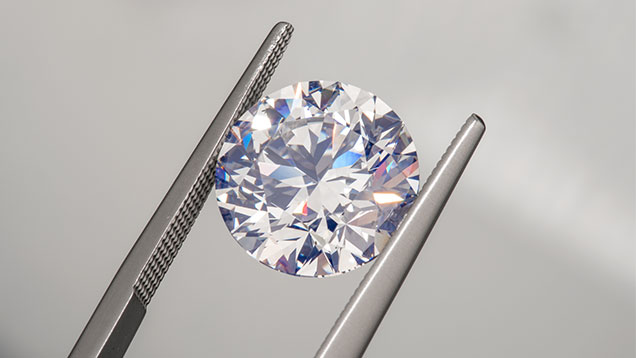A round diamond held by a set of tweezers