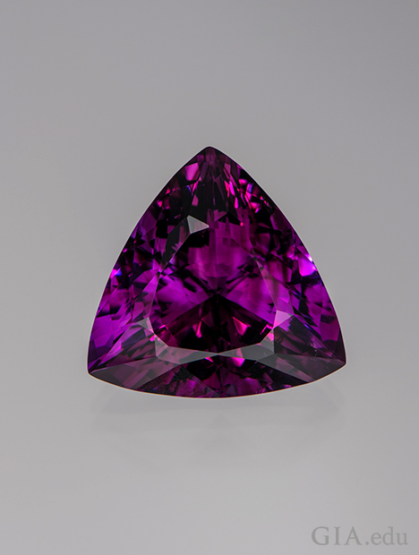 A triangle shaped piece of purple-red amethyst.