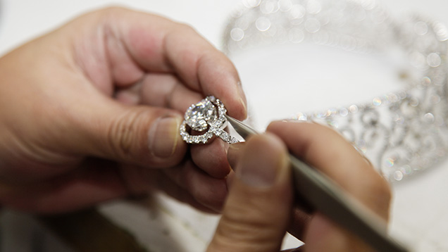 worker making final adjustments on a high-end diamond jewelry suite