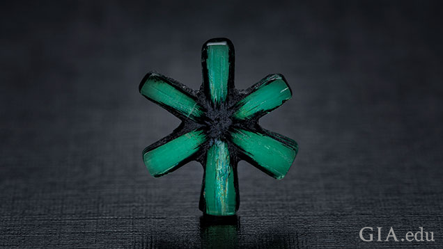 The six-spokes of a trapiche emerald remain after the carbonaceous material is cut away.