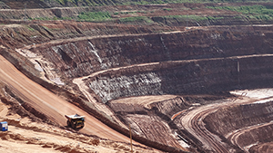 A truck travel the circular roadways of the large mine.