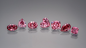 A row of various shaped cut and polished pink diamonds.