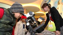 一个小男孩透过显微镜观看宝石。