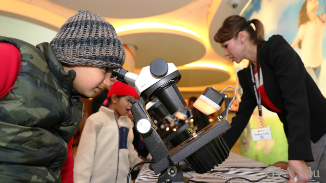A young boy looks through a microscope.