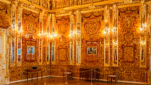 Two sections of the reconstructed Amber Room wall show the mirrored pilasters that separate the panels, the Florentine mosaics, and the intricate amber wreaths and clusters on and atop the cornice.