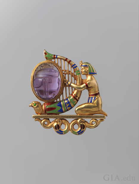 A kneeling figure clad in Egyptian headdress, arm bands, and loincloth playing a falcon-headed harp set with an oval amethyst carved as a scarab. The figure and harp rest on a plinth supported by two coiled snakes. Green, blue, and red enamel accent the h