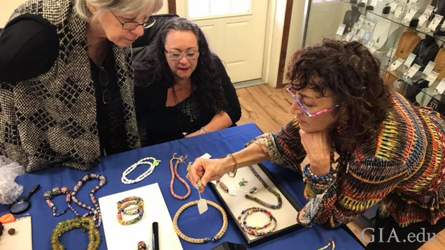 A group of three women gather around a table to look at beaded jewellery.