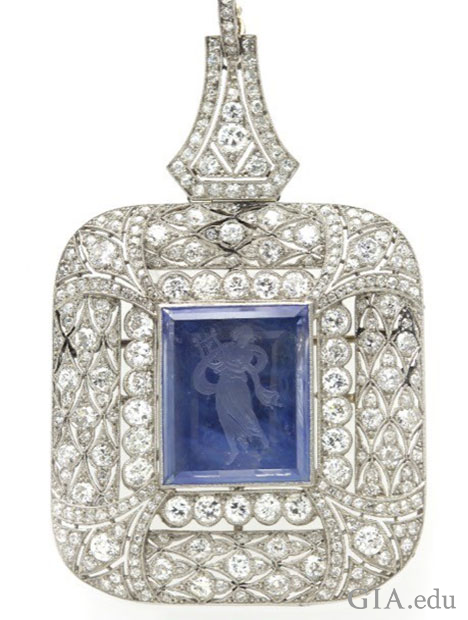 A square shaped pendant with a center reverse intaglio sapphire that is surrounded by diamonds.