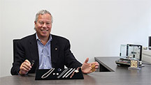 Man sits at his desk with a display stand of multiple pieces of jewelry in front of him.