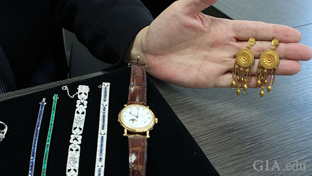 A tray of jewelry pieces sits on the desk and a hand holds a pair of Castellani earrings.