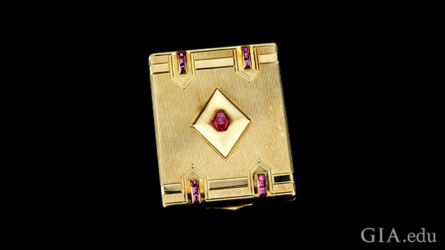Gold compact embellished with synthetic rubies.