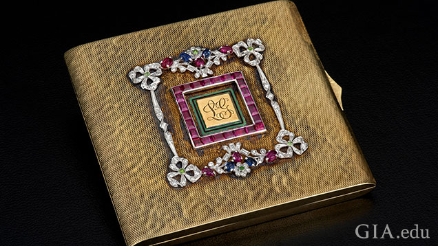 Square, gold compact embellished with garnets and diamonds.