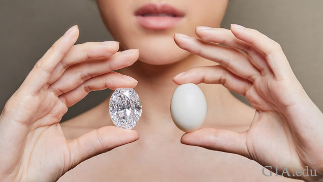 A model holds the diamond in one hand and a pigeon egg in the other.