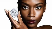 モデルが3本の指で大きな隅切りスクエアのダイヤモンドを持っている。