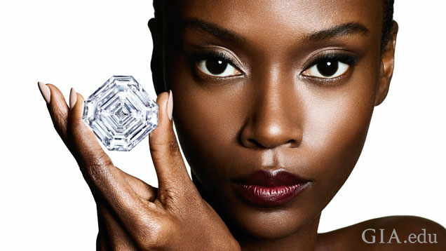 A model holds a large cut-corner square diamond with three fingers.
