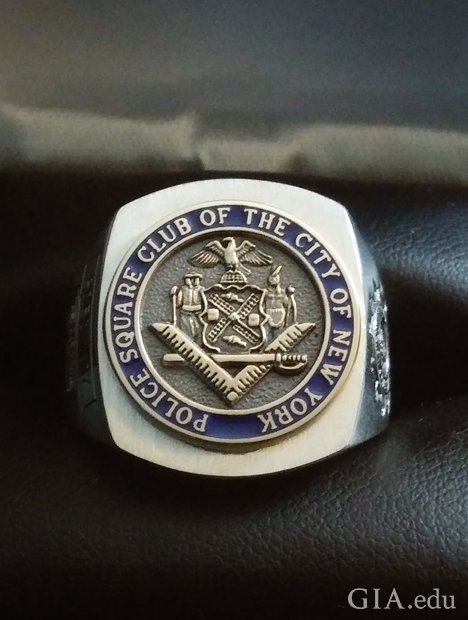 "A square-shaped ring with a circular centre with raised symbols. It is engraved with ""Police Square Club of the City of New York""."