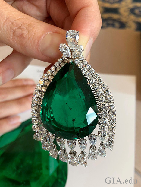 A pear-shaped emerald framed by two rows of various sized diamonds.