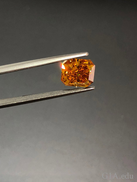 A pair of jewellers tweezers holds an orange diamond.