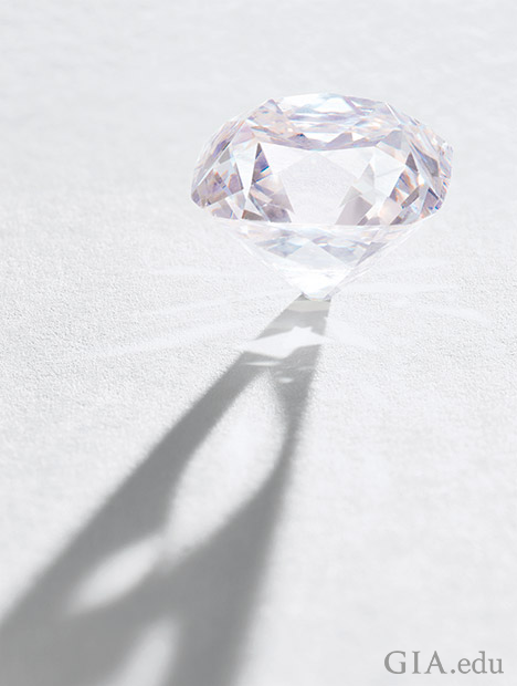 An unmounted light pink diamond stands on its culet.