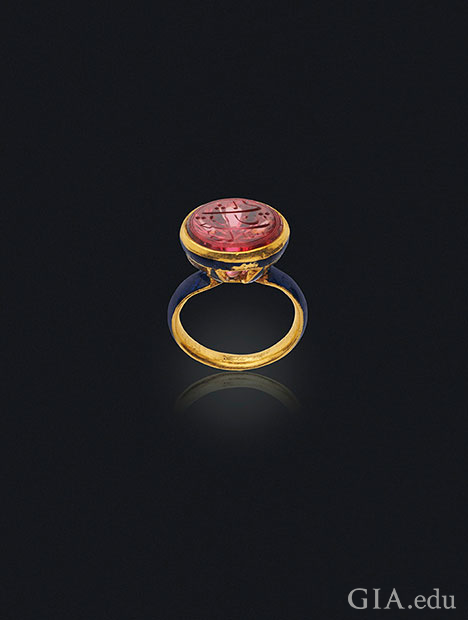 A carved spinel sits on the top of an enamel seal ring.