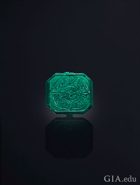 A square shaped emerald with carving on top.