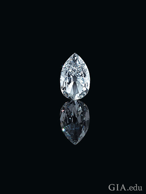 A large pear shaped diamond sits on a black background with its reflection in front of it.