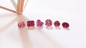 Six different shaped red and pink diamonds lined up in a row.