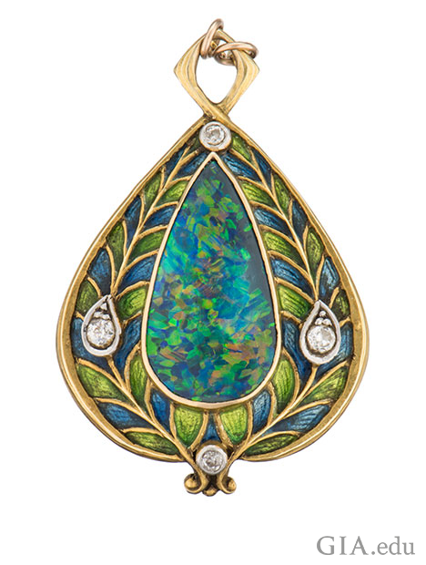 A pear shaped black opal cabochon is enhanced by European-cut diamonds and blue and green enamel applied on 14k gold gold.
