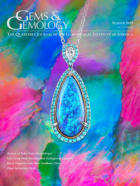 A black opal pendant, accented by pear-shaped diamonds and round Paraíba tourmalines, sits on a photomicrograph of a black opal from Lightning Ridge, Australia, that shows broad, angular flashes of play-of-colour known as a harlequin or mosaic pattern.