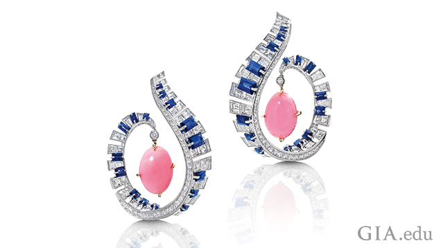 The frames of the earrings are designed as a scroll from which a pink conch pearl dangles. The scrolls are comprised of blue sapphires and diamonds to look like piano keys.