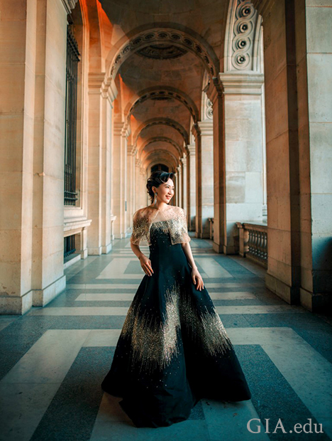 Woman stands in a long, ornate hallway, dressed in formal ballgown.