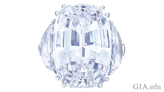 A 46.93 carat cushion step-cut diamond with half-moon modified brilliant-cut diamonds (one 3.64 ct and one 3.35 ct) on its sides.