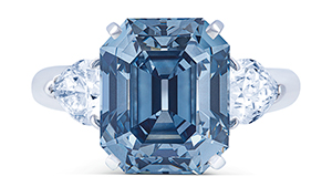 A rectangular cut Fancy Deep blue diamond is framed by two pear shaped diamonds.