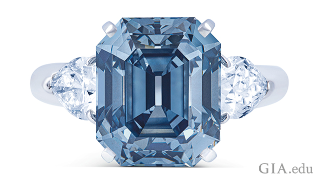 A rectangular cut Fancy Deep blue diamond is framed by two pear-shaped diamonds.