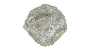 A piece of diamond rough with green body color and triangular etchings on the surface.