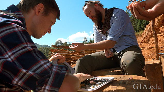 Two men sort through gem gravel on site.