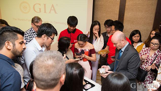テーブルを囲んで、真珠と母貝の試料を観察する人々。