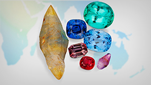 An array of rough and polished colored gemstones sitting on a world map.