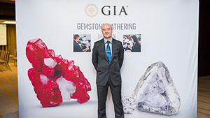 Man stands in front a GIA banner that features gemstones.