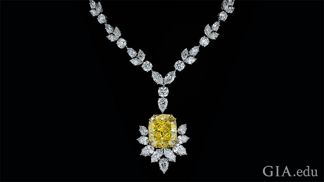 A large yellow cushion cut diamond pendant is partially framed with marquis cut diamonds and hangs from a necklace of mixed cut diamonds.
