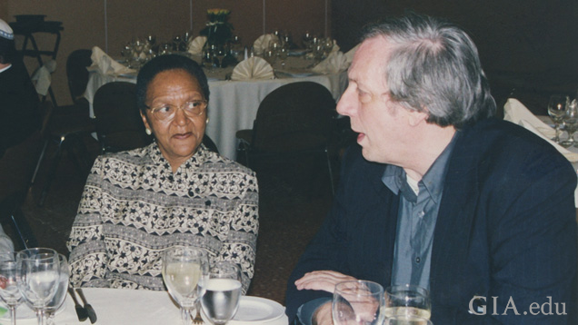 A woman and man sit at a dinner table talking.