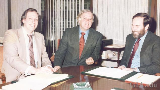 会議室のテーブルを囲む3人の男性。