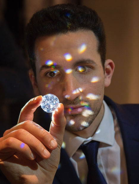 Photo of a man holding a large round diamond with reflections from the diamond.